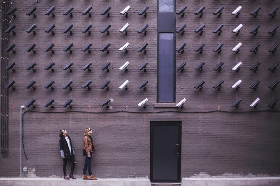 Many CCTV cameras point at two women by a building entrance